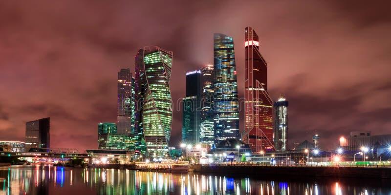 A cidade de Moscou na noite, vista da terraplenagem do rio de Moscou ao distrito financeiro Arquitetura e marco de M fotografia de stock
