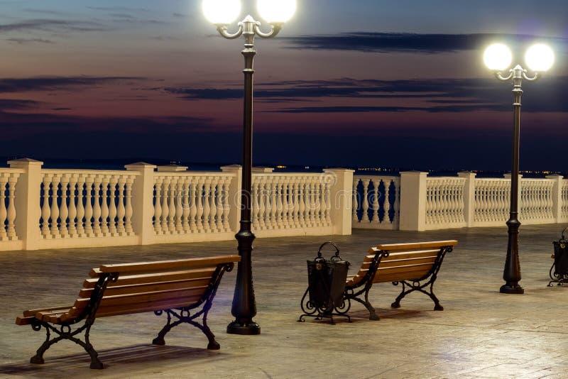 Cidade de nivelamento bonita com luzes brilhantes e um banco bonito na estrada fotografia de stock royalty free