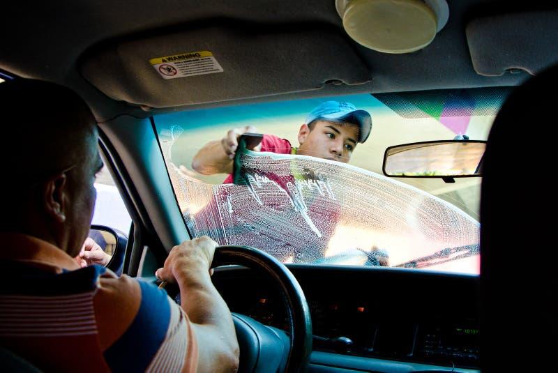 Cidade do México, México - 12 de abril de 2012 Janela de carro de limpeza do homem em luzes da estrada transversaa foto de stock