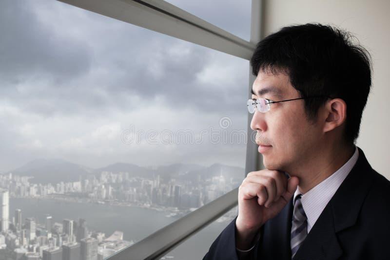 Cidade do olhar do homem de negócio através da janela foto de stock royalty free