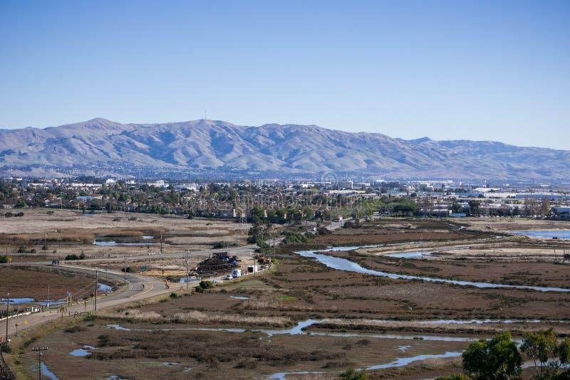 Cidade e região pantanosa na área de San Francisco Bay sul; Picos da missão, do monumento e do Allison na cordilheira de Diablo n imagem de stock