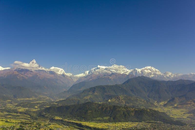 Cidade em um vale verde-claro da montanha no fundo de montes arborizados e de picos nevados de Annapurna com as nuvens brancas so imagens de stock royalty free