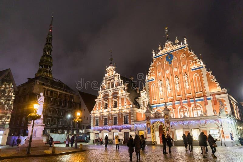 Cidade Hall Square com a casa da igreja na cidade velha de Riga na noite durante o Natal, Letónia das pústulas e do St Peter fotos de stock royalty free