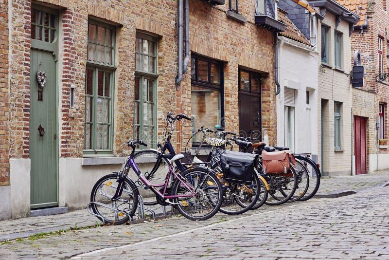 Cidade medieval tradicional Rua pavimentada estreita com as casas e as bicicletas velhas do tijolo perto da entrada fotografia de stock