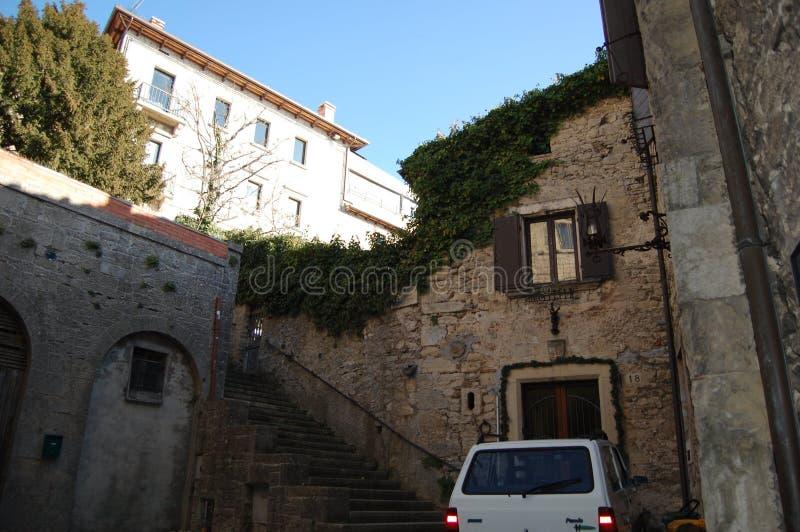 A cidade na montanha é São Marino Para salvar o espaço, a casa foi construída como uma continuação da parede da cidade imagens de stock royalty free
