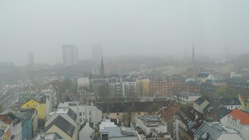 Cidade na névoa, skyline da cidade da névoa, ambiente crítico da poluição do ar em cima do distrito do centro do balcão em Hambur foto de stock