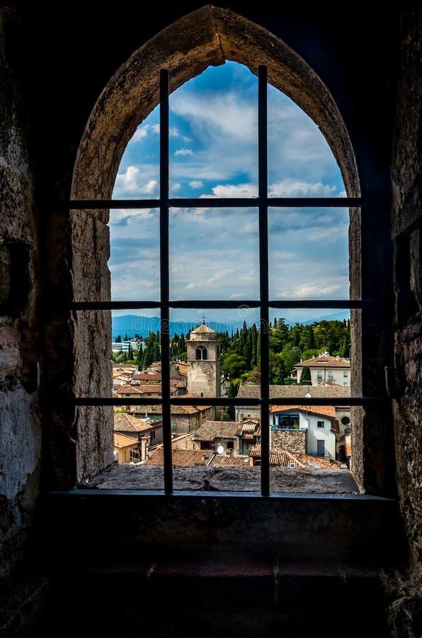 A cidade pitoresca pequena Sirmione pelo lago Garda em Itália moldou em uma janela imagens de stock royalty free