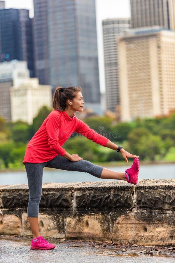 Cidade que corre a mulher saudável do corredor do estilo de vida que estica o exercício de pés para correr no fundo urbano Curso  imagens de stock