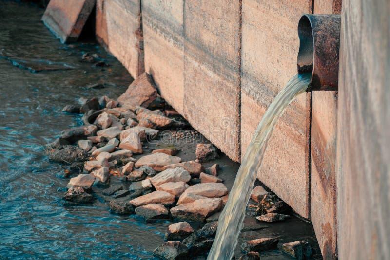 Cidade que polui o ambiente Tubulação da drenagem que descarrega produtos da cintura diretamente no rio foto de stock