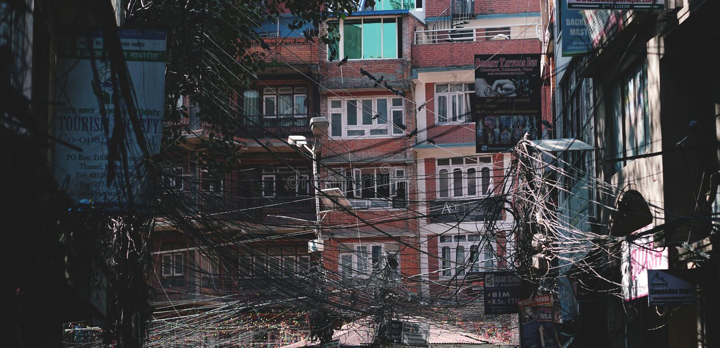 Cidade Scape de Thamel, construção coberta pelo cabo de fio do caos imagem de stock