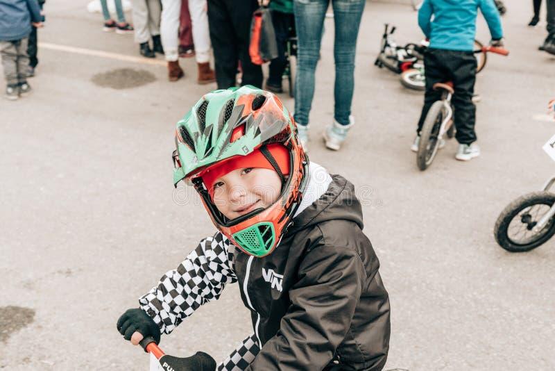 Cidade Tula Rússia - 6 de abril de 2019: rapaz pequeno em um capacete protetor na competição amadora das crianças equilibrar a bi fotografia de stock