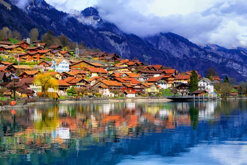 Cidade velha e montanhas dos cumes que refletem no lago, Su??a imagem de stock