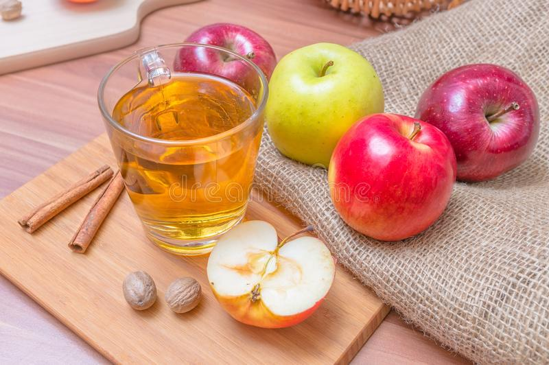 Cider - alcohol hot apple drink and apples on wooden table.  royalty free stock photo