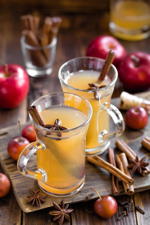 Cider. Apple cider with cinnamon and anise in two glasses on a wooden table stock images