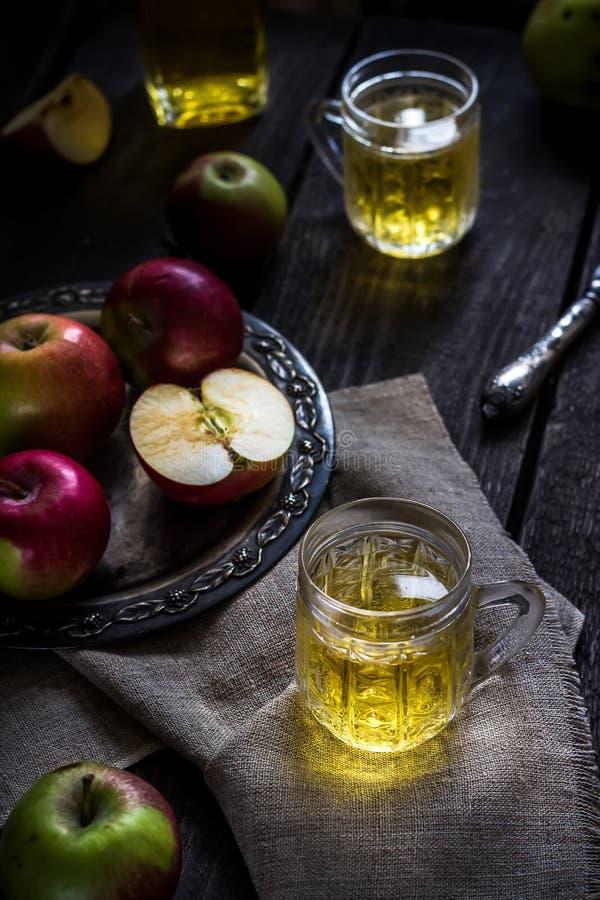 Cider en appelen op oud metaaldienblad Donkere houten lijst royalty-vrije stock afbeelding