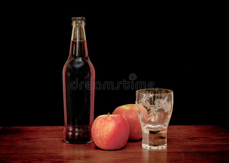 Cider. Still life of a bottle of cider with glass and apples royalty free stock photos
