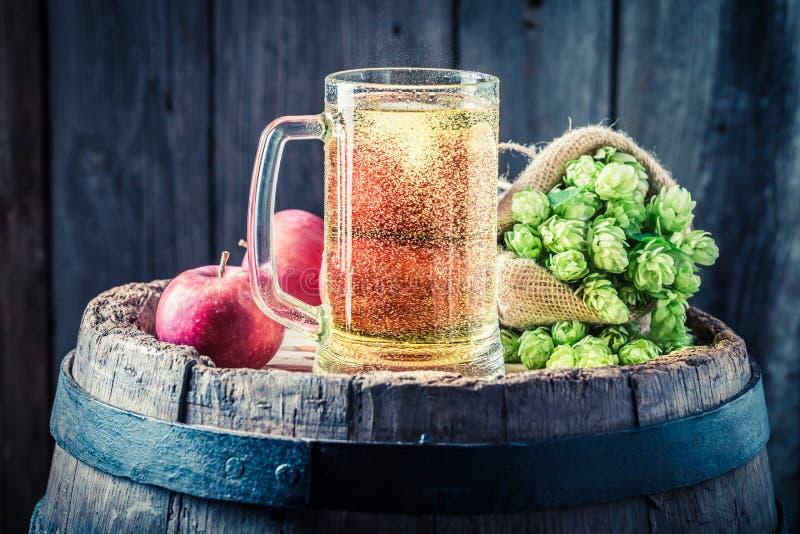 Ciderbier met appelen, hop en tarwe op oud vat stock foto's