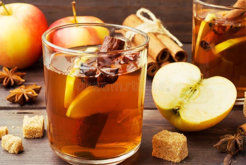 Cidre de vin chaud dans des tasses en verre avec de la cannelle, l'anis et les pommes Le concept de la barre de cocktail photographie stock