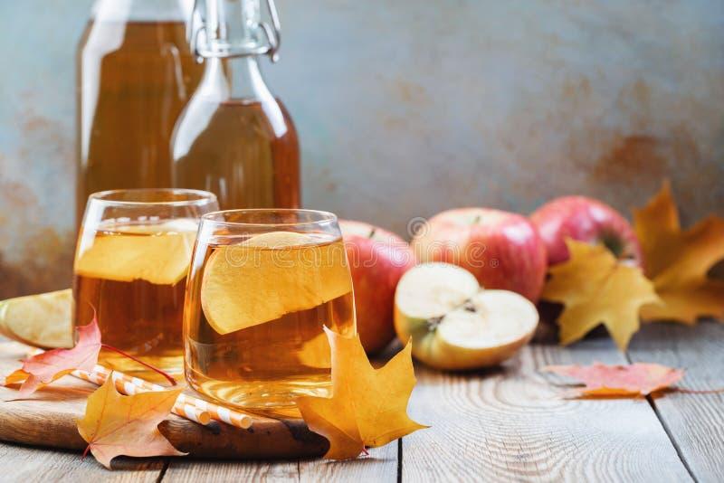 Cidre ou jus de pommes organique sur une table en bois avec l'espace de copie Deux verres avec des feuilles de boissons et d'auto images libres de droits