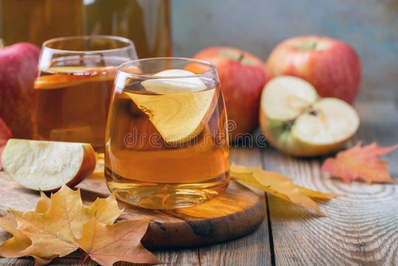 Cidre ou jus de pommes organique sur une table en bois Deux verres avec des feuilles de boissons et d'automne sur le fond rustiqu photographie stock