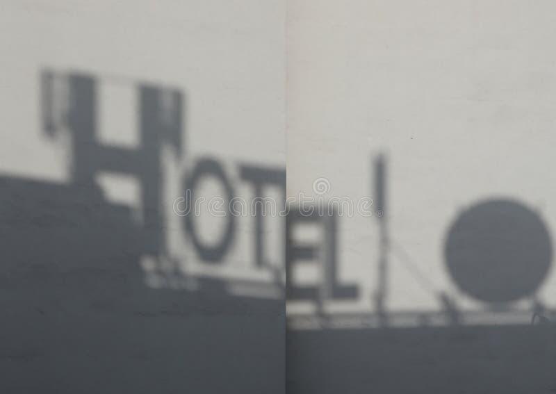 Cień hotelowa znak deska na betonowej ścianie w zmierzchu świetle obrazy royalty free