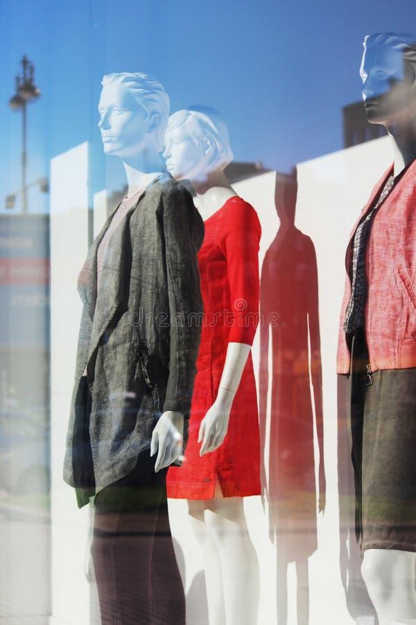 Cień kobiety ` s mannequin w czerwonej sukni, mężczyzna i kobiecie w modnych kostiumach w sklepowym okno, fotografia stock
