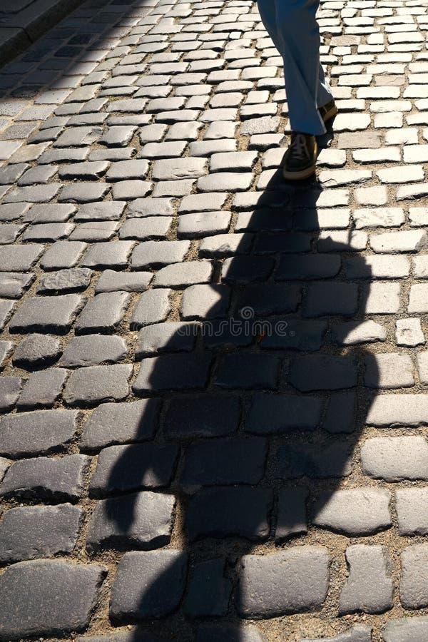Cień nadchodzący pedestrians na brukowach obraz royalty free