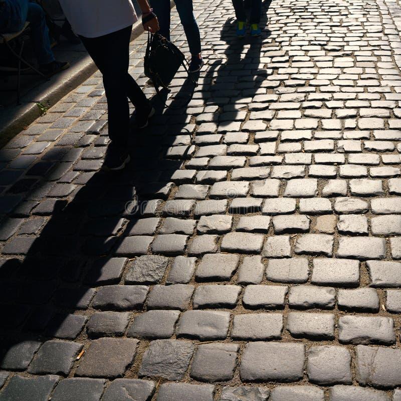 Cień nadchodzący pedestrians na brukowach obrazy royalty free