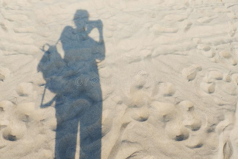 Cień osoba z kamerą i plecakiem na piaskowatym brzeg fotografia stock