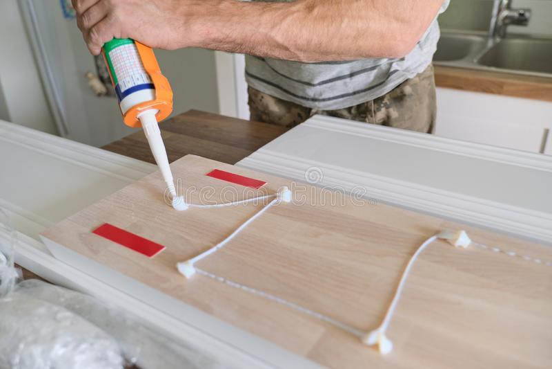 Cieśla budowy męski używa kleidło, gdy pracujący z drewnianym bielem malował deskę, zbliżenie, ciesielka, woodwork, zawód zdjęcie stock