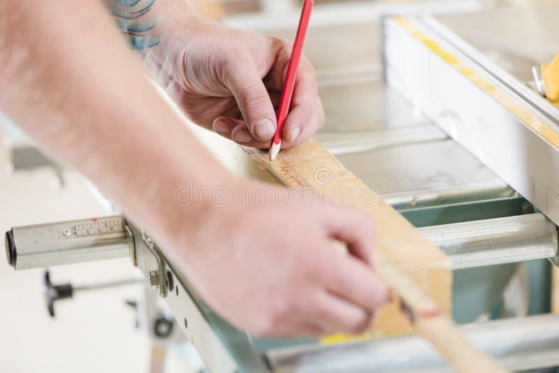 Cieśla mierzy długość drewniana deska przed piłować obraz stock