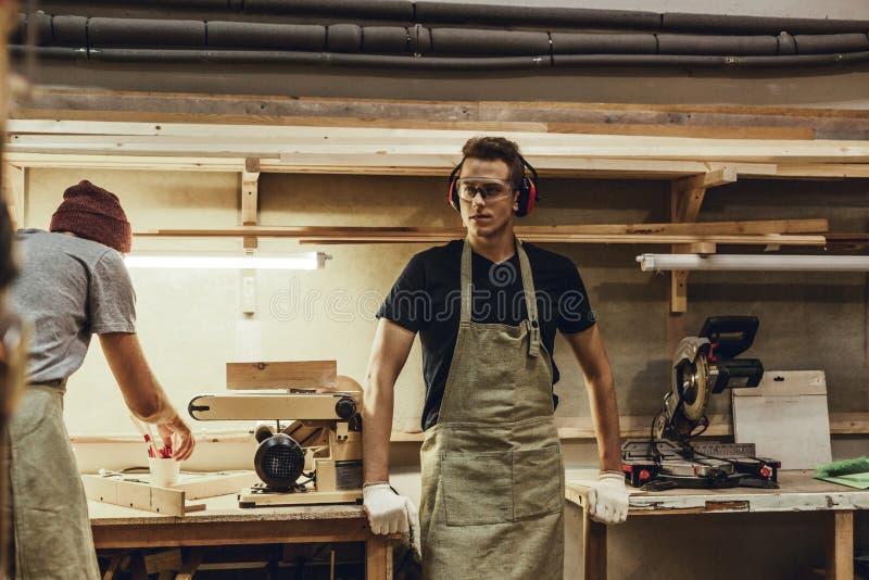 Cieśla opiera na workbenches i patrzeje daleko od fotografia stock