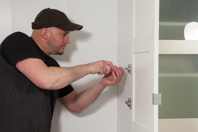 Cieśla pracuje na nowej garderobie Złota rączka załatwia drzwi w garderobie obraz stock