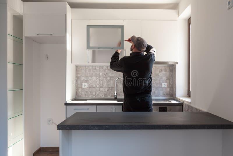 Cieśla pracuje na nowej kuchni Złota rączka załatwia drzwi w kuchni zdjęcia stock