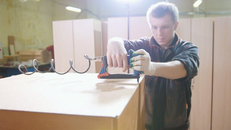 Cieśla pracuje z elektrycznym przemysłowym zszywaczem na fabryce, załatwia meblarskich szczegóły, zakończenie obraz royalty free