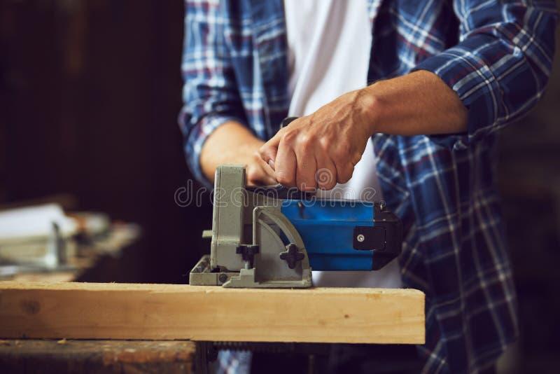 Cieśla używa kurendę zobaczył dla ciąć drewnianą deskę zdjęcia stock