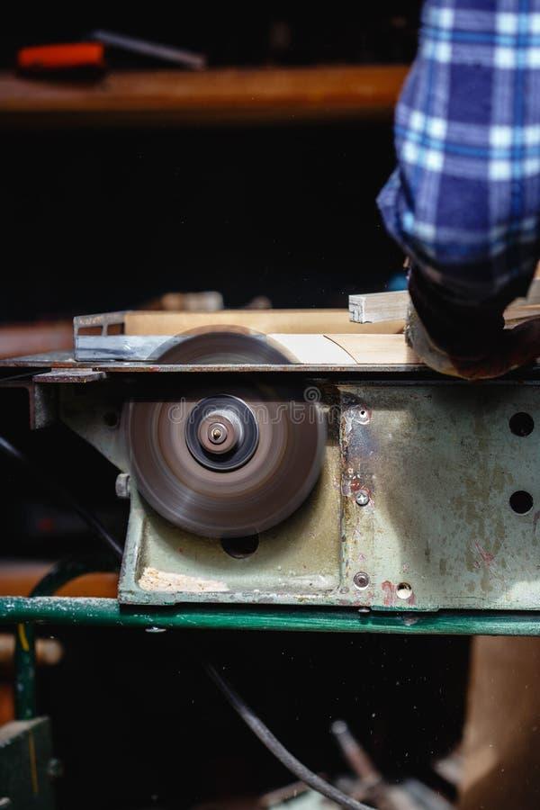 Cieśla używa kurendę zobaczył tnącą drewnianą deskę w drewnianym warsztacie fotografia royalty free