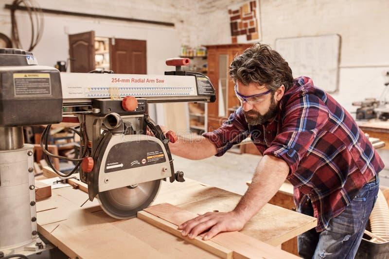 Cieśla używa promieniową rękę zobaczył ciąć drewno w warsztacie zdjęcie royalty free