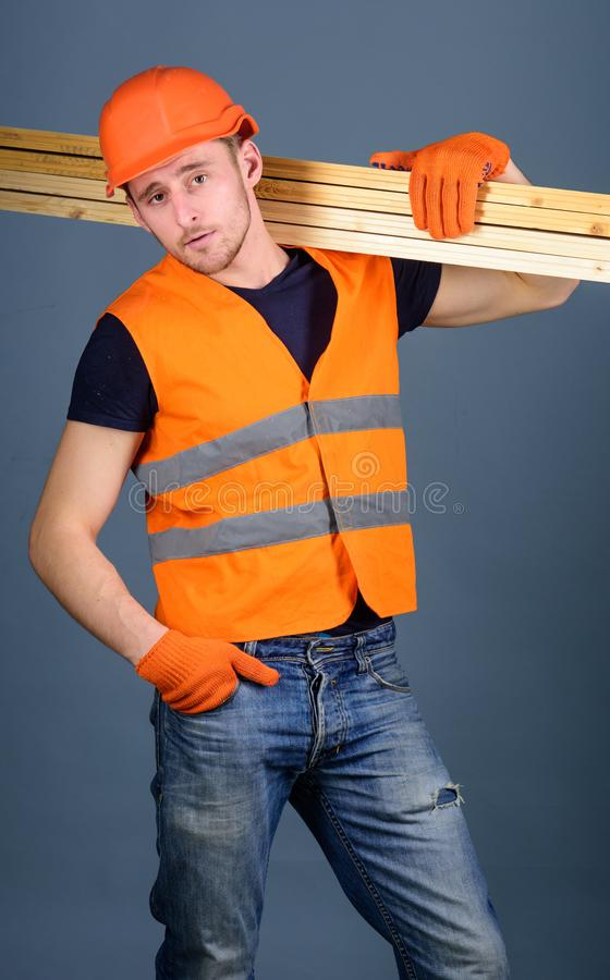 Cieśla, woodworker, robotnik, budowniczy na ufnej twarzy niesie drewnianych promienie na ramieniu Mężczyzna w hełmie, ciężki kape zdjęcie stock
