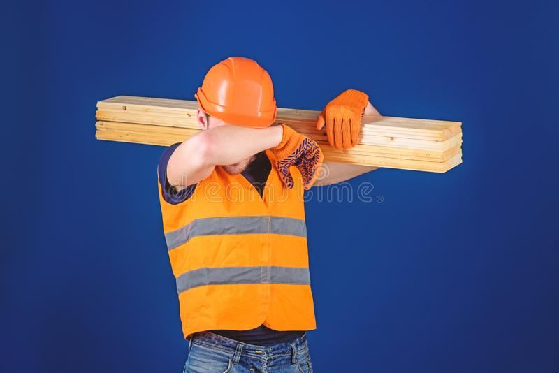 Cieśla, woodworker, robotnik, budowniczy na zmęczonej twarzy niesie drewnianego promień na ramieniu Zmęczony robotnika pojęcie mę zdjęcia stock