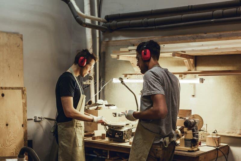 Cieśle stoi blisko workbench w earmuffs zdjęcie royalty free