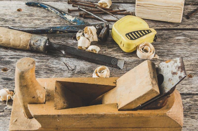 Cieśli narzędzia na drewnianej ławce, samolocie, ścinaku, dobniaku, taśmy miarze, młocie, tongs, cążkach, poziomie, gwoździach i  zdjęcie royalty free