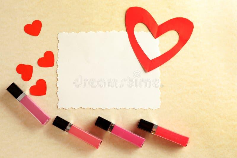 Ciekłe pomadki z pustej karty i czerwieni sercami na koloru tle zdjęcie royalty free