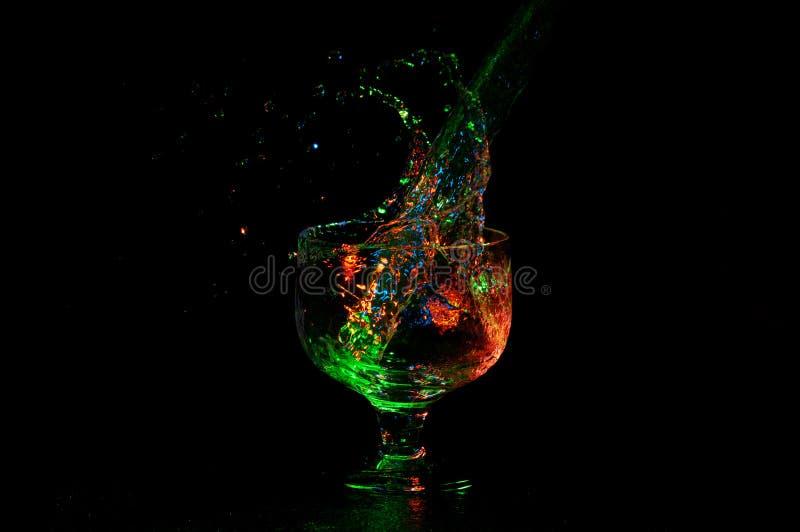 Ciekły chełbotanie od za szkle z trzonem z wibrującymi barwionymi światłami na czerni obrazy royalty free
