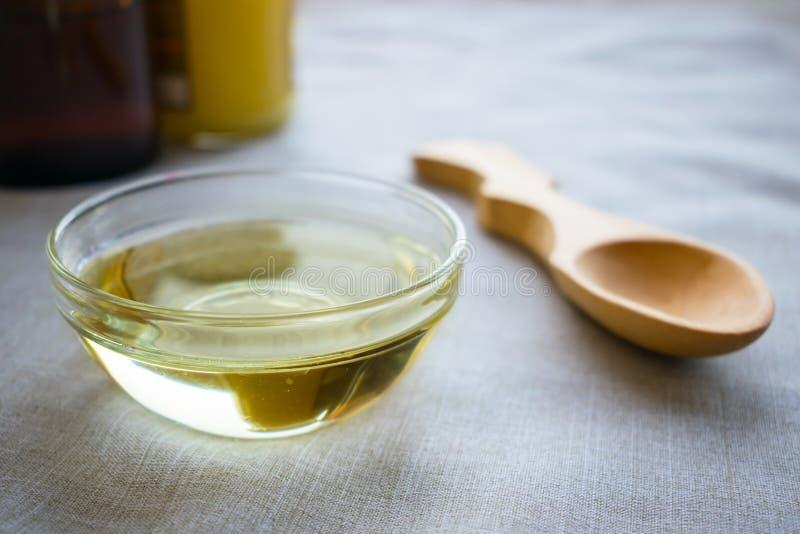 Ciekły koksu MCT olej w round szklanym pucharze z drewnianą łyżką i zdjęcie stock