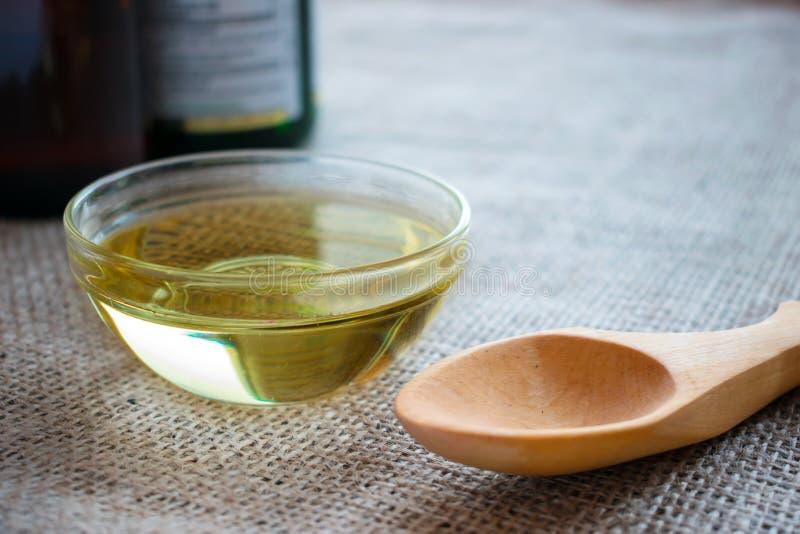 Ciekły koksu MCT olej w round szklanym pucharze z drewnianą łyżką i obraz stock