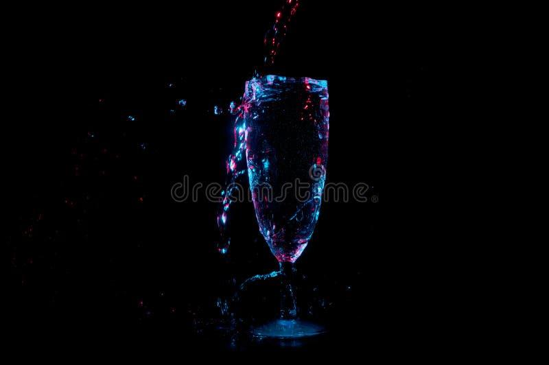 Ciekły lśnienie w, chełbotanie w szampańskiego flet odizolowywającego na czarnym tle i obraz royalty free