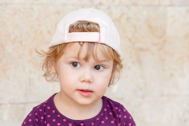 Ciekawa śliczna blond dziewczynka w białej baseball nakrętce obraz stock