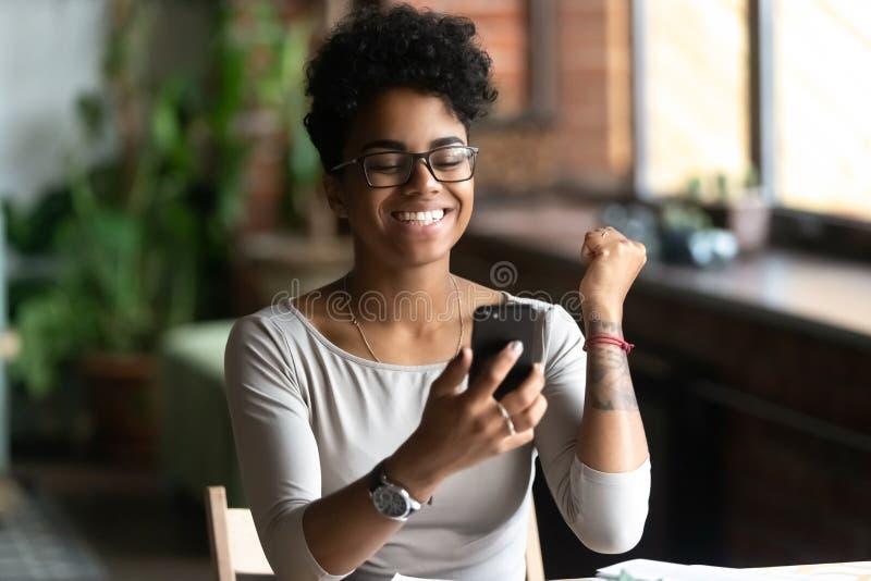 Ciekawa czarna dziewczyna czuje euforiÄ™ czytajÄ…c wiadomoÅ›ci na komórce zdjęcia royalty free