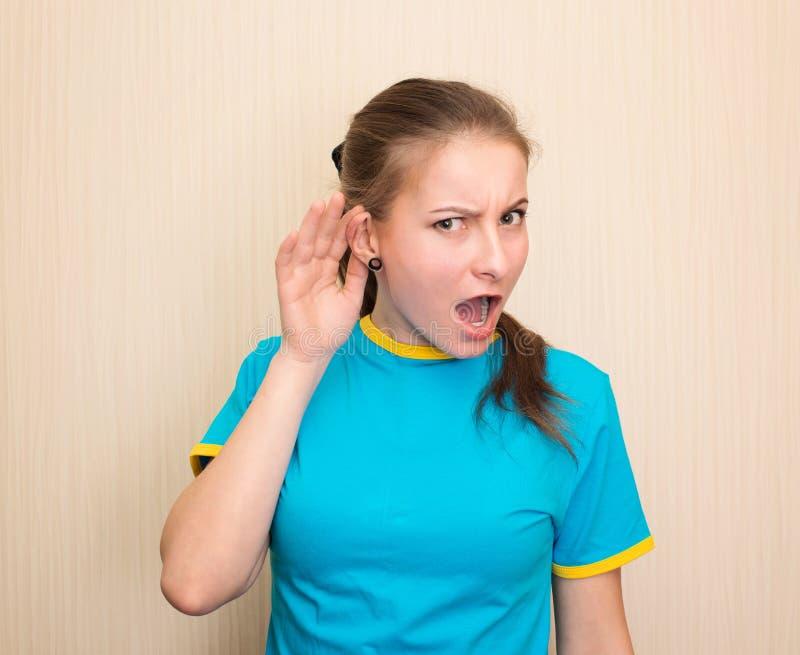 Ciekawa dziewczyna słucha Zamykanie portretu nastolatka słyszącego coś, plotki, gesty trzymane w ręku, izolowane Ekspresja twarzy fotografia stock